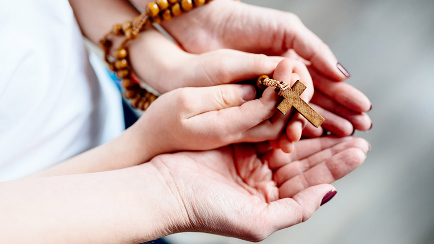 A mother and her child praying together the Rosary