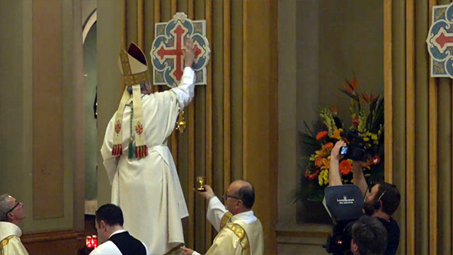 Archbishop Lépine, ointing one of the 12 crosses of consecration during the celebration.