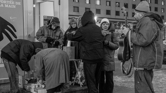 Father Paradis giving food to the homeless during winter